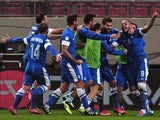 Greece's Kostas Mitroglou celebrates with teammates after scoring during the 2014 FIFA World Cup qualifying play-off first leg football match between Greece and Romania at the Karaiskaki stadium in Athens on November 15, 2013
