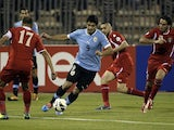 Luis Suarez of Uruguay dribbles between three Jordan defenders during their World Cup qualifier in Amman on November 13, 2013