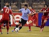 Luis Suarez of Uruguay dribbles between three Jordan defenders during their World Cup qualifier in Amman on November 13, 2013