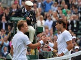 Rafael Nadal and Steve Darcis embrace at the net after the latter wins their match at Wimbledon on June 24, 2013.