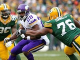 Adrian Peterson of the Minnesota Vikings is hit by Mike Daniels of the Green Bay Packers at Lambeau Field on November 24, 2013