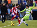 Atletico Madrid's Arda Turan vies with Getafe's Michel during the Spanish League football match on November 23, 2013