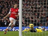 Arsenal's French striker Olivier Giroud scores scores the opening goal after tackling Southampton's Polish goalkeeper Artur Boruc during the English Premier League football match between Arsenal and Southampton at the Emirates Stadium in London on Novembe