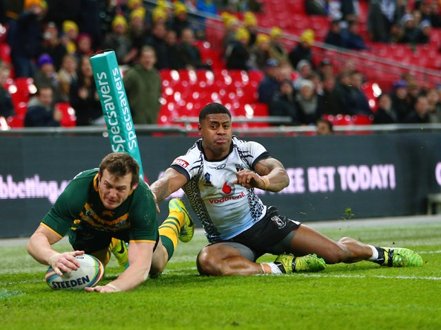 Brett Morris of Australia scores a try as Kevin Naiqama of Fiji challenges during the Rugby League World Cup Semi Final match between Australia and Fiji at Wembley Stadium on November 23, 2013