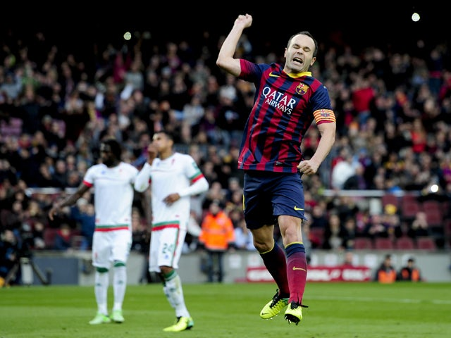 Barcelona's midfielder Andres Iniesta celebrates after scoring during the Spanish league football match FC Barcelona vs Granada CF at the Camp Nou stadium in Barcelona on November 23, 2013