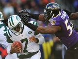 Quarterback Geno Smith of the New York Jets is hit by outside linebacker Elvis Dumervil of the Baltimore Ravens during the first half at M&T Bank Stadium on November 24, 2013