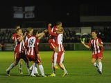 Glenn Walker of Brackley Town celebrates with Curtis McDonald (3) and team-mates after scoring during the FA Cup First Round Replay match against Gillingham on November 18, 2013