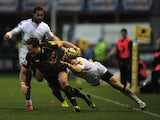 James Wilson of Northampton Saints is tackled by Alex Tait of Newcastle Falcons during the Aviva Premiership match between Northampton Saints and Newcastle Falcons at Franklin's Gardens on November 23, 2013