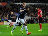 Man United's Patrice Evra celebrates with teammate Jonny Evans after scoring his team's second goal against Cardiff on November 24, 2013