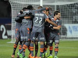 Lorient forward Vincent Aboubakar is congratulated by his teammates after scoring against Evian on November 23, 2013