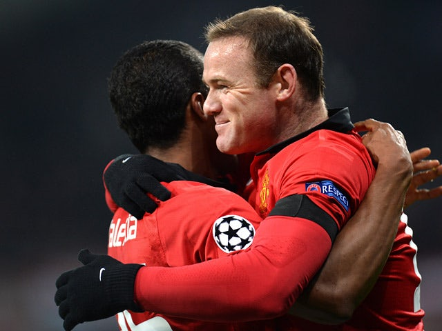 Man United's Antonio Valencia is congratulated by teammates Wayne Rooney after scoring the opening goal against Bayern Leverkusen during their Champions League group match on November 27, 2013