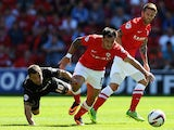 Shaun Maloney of Wigan Athletic and Chris Dagnall of Barnsley challenge for the ball during the Sky Bet Championship match between Barnsley and Wigan Athletic at Oakwell on August 03, 2013