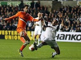 Swansea's Chico Flores and Valencia's Jonas battle for the ball during their Europa League group match on November 28, 2013