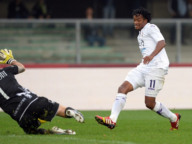 Juan Guillermo Cuadrado of ACF Fiorentina scores his team's first goal past AC Chievo goalkeeper Christian Puggioni to equalise during the Serie A match between AC Chievo Verona and ACF Fiorentina at Stadio Marc'Antonio Bentegodi on October 27, 2013