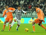 Carlos Tevez of Juventus is challenged by Allan Marques of Udinese Calcio during the Serie A match between Juventus and Udinese Calcio at Juventus Arena on December 1, 2013