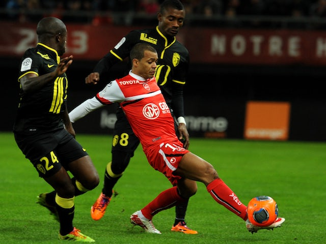 Valenciennes's Mathieu Dossevi vies with Lille's Salomon Kalou and Rio Mavuba during a French L1 football match on November 30, 2013