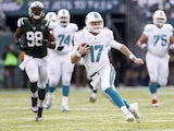 Ryan Tannehill #17 of the Miami Dolphins runs for a first down against the New York Jets during their game at MetLife Stadium on December 1, 2013