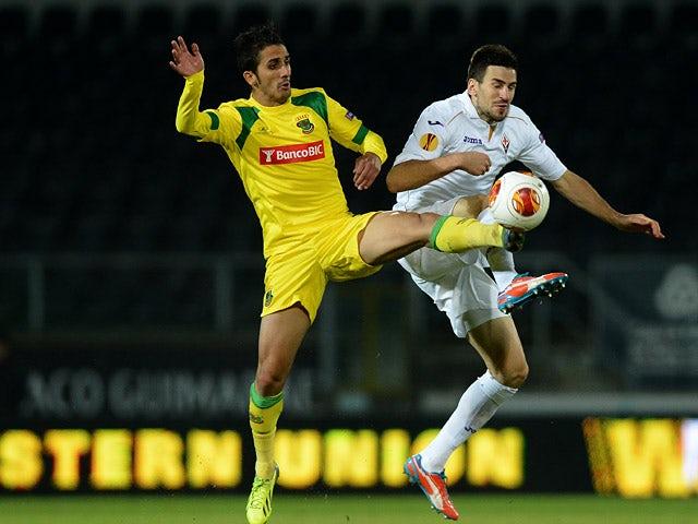 Pacos Ferreira's Ruben Ribeiro and Fiorentina's Nenad Tomovic battle for the ball during their Europa League group match on November 28, 2013