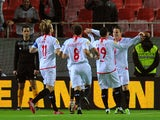 Sevilla's French forward Kevin Gameiro celebrates with his teammates after scoring during the UEFA Europa League football match Sevilla FC vs Estoril Praia at the Ramon Sanchez Pizjuan stadium in Sevilla on November 28, 2013