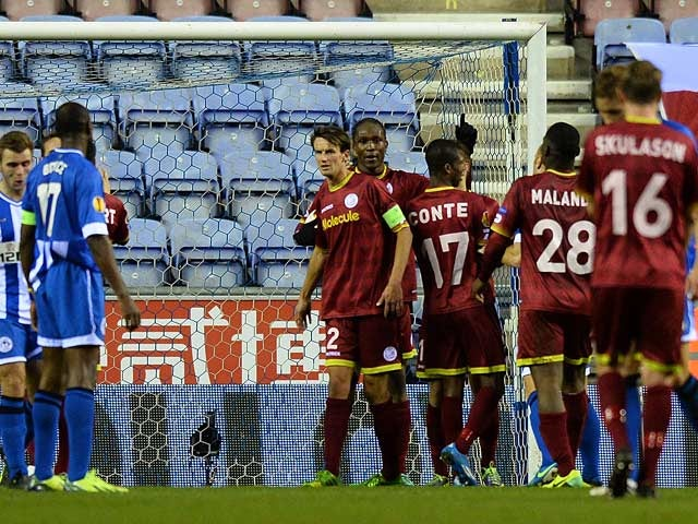 Zulte Waregem's Thorgan Hazard is congratulated by teammates after scoring his team's opening goal against Wigan during their Europa League group match on November 28, 2013