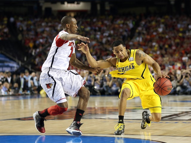 Trey Burke #3 of the Michigan Wolverines drives against Russ Smith #2 of the Louisville Cardinals during the 2013 NCAA Men's Final Four Championship at the Georgia Dome on April 8, 2013