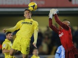 Villarreal's Brazilian defender Gabriel Paulista vies with Malaga's Argentinian goalkeeper Willy Caballero during the Spanish league football match Villareal CF vs Malaga at El Madrigal stadium in Villarreal on November 29, 2013