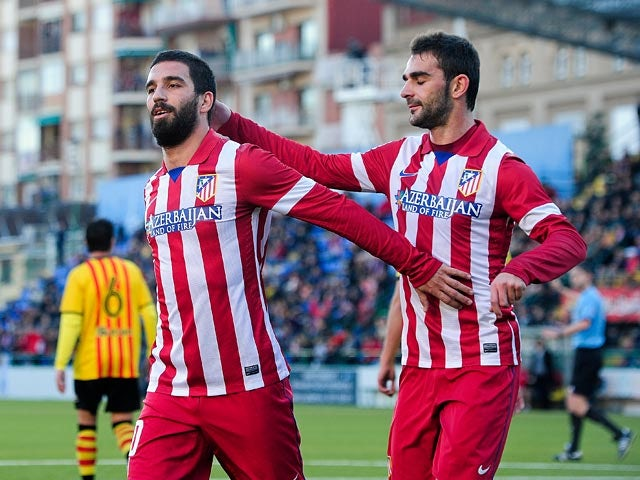 Atletico Madrid's Arda Turan celebrates with teammate Adrian Lopez after scoring his team's second goal against Sant Andreu during their Copa del Rey on December 7, 2013
