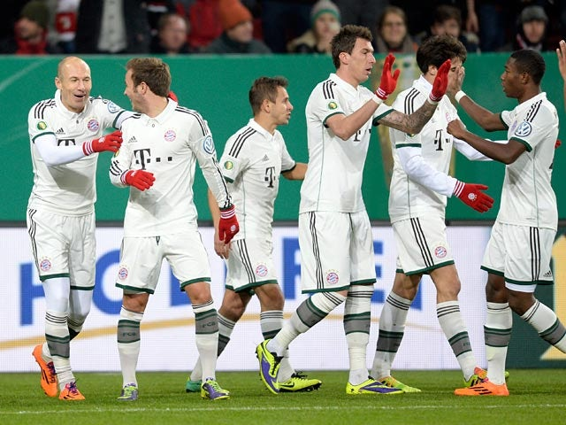 Bayern Munich's Arjen Robben is congratulated by teammates after scoring the opening goal against Augsburg during their 3rd round German Cup match on December 4, 2013