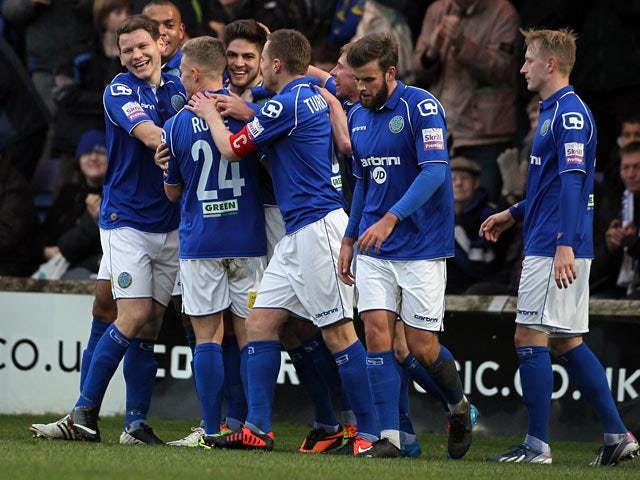 Macclesfield's Danny Andrew is congratulated by teammates after scoring the opening goal against Brackley during their FA Cup second round match on December 7, 2013