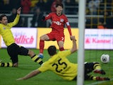 Leverkusen's South Korean striker Heung Min Son scores past Dortmund's defender Manuel Friedrich and Dortmund's Greek defender Sokratis during the German first division Bundesliga football match Borussia Dortmund vs Bayer Leverkusen in the western German