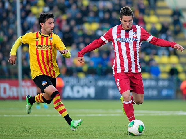 Sant Andreu's Ibon and Atletico Madrid's Koke in action during their Copa del Rey match on December 7, 2013