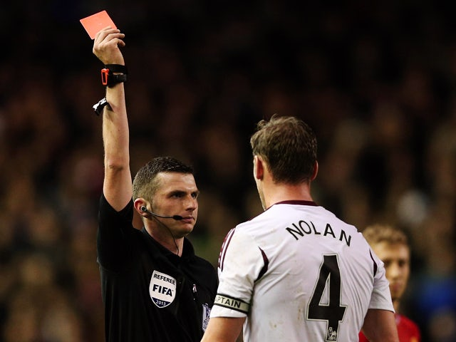 Kevin Nolan of West Ham United is shown a red card by Referee Michael Oliver during the Barclays Premier League match between Liverpool and West Ham United at Anfield on December 7, 2013