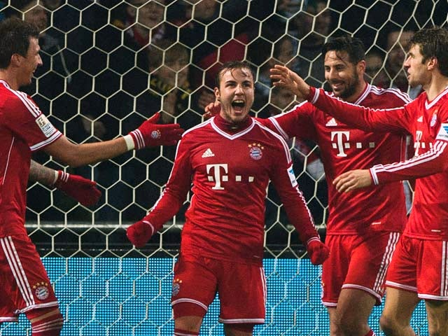 Bayern's Mario Gotze celebrates with teammates after scoring his team's seventh goal against Werder Bremen during their Bundesliga match on December 7, 2013