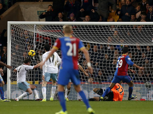 Crystal Palace striker Marouane Chamakh heads into the net for the opening goal during the English Premier League football match on December 3, 2013