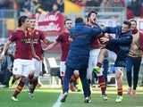 Roma's Mattia Destro celebrates with teammates after scoring his team's second goal against Fiorentina during their Serie A match on December 8, 2013