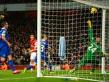 Arsenal's Mesut Ozil heads in the opening goal against Everton during their Premier League match on December 8, 2013