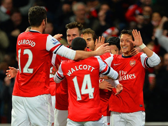 Arsenal's Mesut Ozil celebrates with teammates after scoring the opening goal against Everton during their Premier League match on December 8, 2013