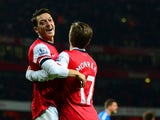 Arsenal's Mesut Ozil celebrates with teammate Nacho Monreal after scoring his team's second goal against Hull during their Premier League match on December 4, 2013