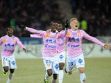 Evian's Modou Sougou celebrates with teammates after scoring his team's second goal against PSG during their Ligue 1 match on December 4, 2013