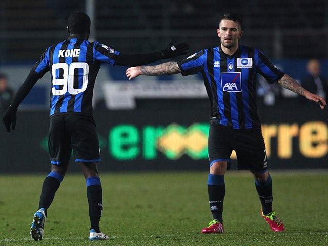 Atalanta's Moussa Kone celebrates with teammate Marko Livaja after scoring the opening goal against Sassuolo Calcio during their Coppa Italia match on December 4, 2013