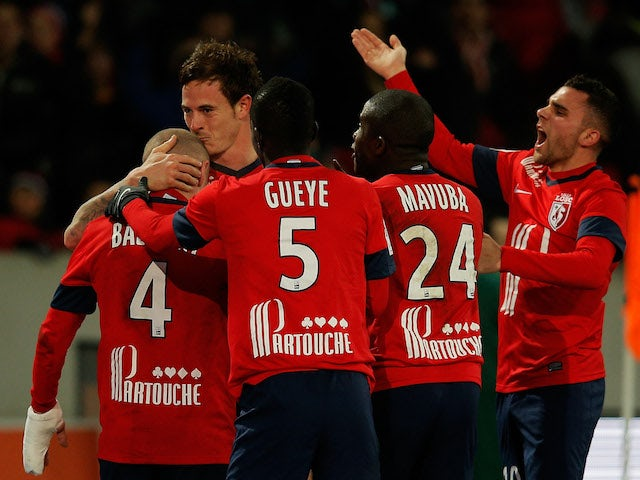 Nolan Rouxof Lille celebrates with teammates after he scores the first goal of the game in the final minutes by kissing Florent Balmont on the head during the Ligue One match on December 3, 2013