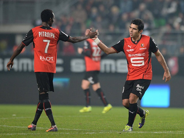Rennes' Silvio Romero is congratulated by teammate Jonathan Pitroipa after scoring the opening goal against Saint Etienne during their Ligue 1 match on December 4, 2013