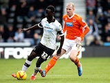 Derby's Simon Dawkins and Blackpool's Neal Bishop in action during their Championship match on December 6, 2013
