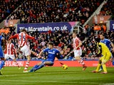Peter Crouch of Stoke shoots past Gary Cahill of Chelsea to score a goal to level the scores at 1-1 during the Barclays Premier League match between Stoke City and Chelsea at Britannia Stadium on December 7, 2013
