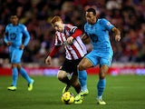 Jack Colback of Sunderland battles with Mousa Dembele of Tottenham during the Barclays Premier League match between Sunderland and Tottenham Hotspur at the Stadium of Light on December 7, 2013