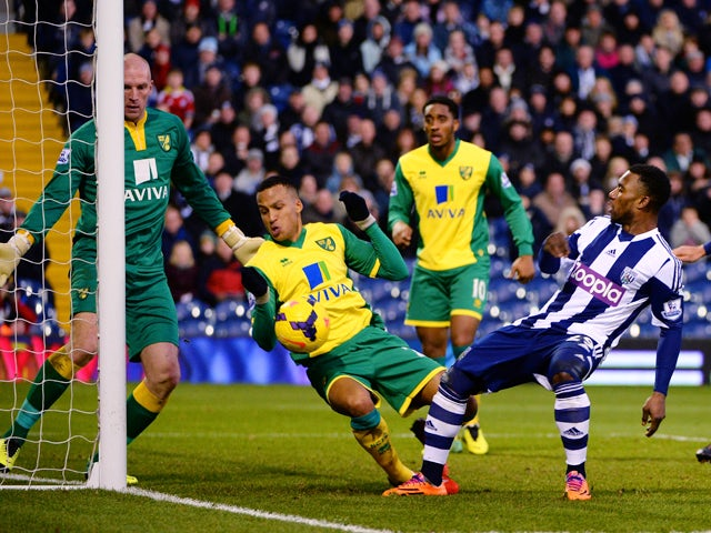 Stephane Sessegnon of West Bromwich has his shot on goal blocked by the arm of Martin Olsson of Norwich during the Barclays Premier League match between West Bromwich Albion and Norwich City at The Hawthorns on December 7, 2013