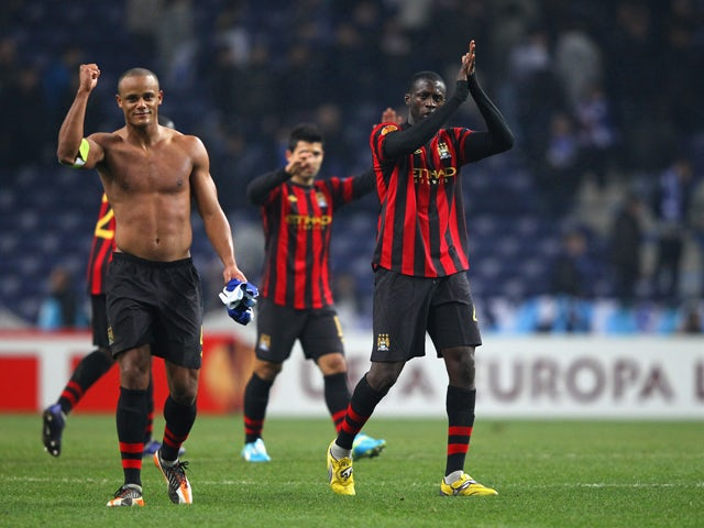 Yaya Toure and Vincent Kompany of Manchester City celebrate after victory over FC Porto in the UEFA Europa League round of 32 first leg match between FC Porto and Manchester City at Estadio do Dragao on February 16, 2012