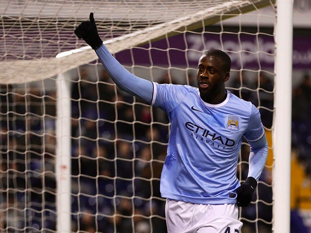 Man City's Yaya Toure celebrates after scoring his team's third goal via the penalty spot against West Brom during their Premier League match on December 4, 2013