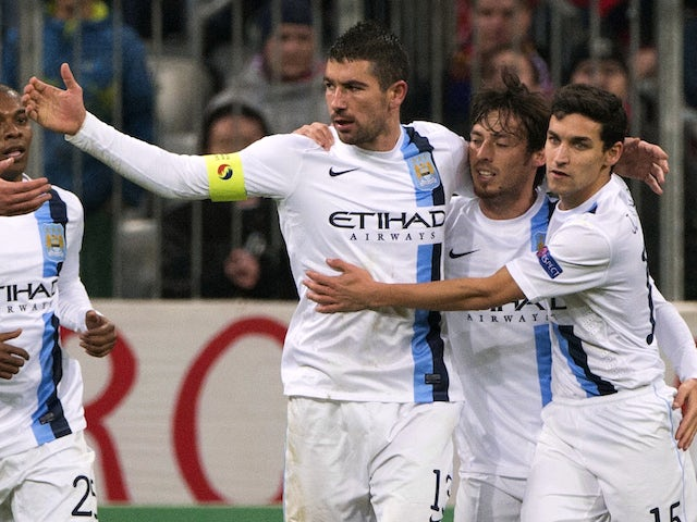 Manchester City players celebrate after Serbian defender Aleksandar Kolarov scored through a penalty kick during the UEFA Champions League group D football match against Bayern Munich on December 10, 2013