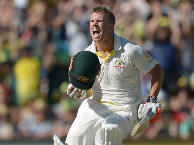 Australian batsman David Warner celebrates making his 100 runs on the third day of the third Ashes cricket Test match against England in Perth on December 15, 2013